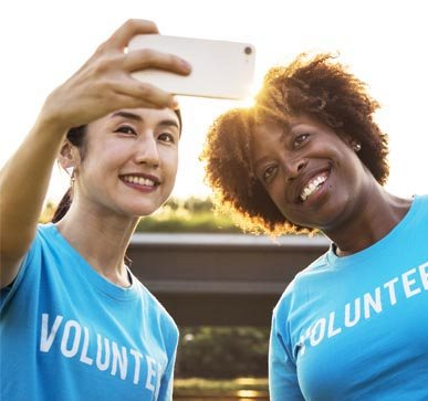 Two smiling volunteers taking a selfie